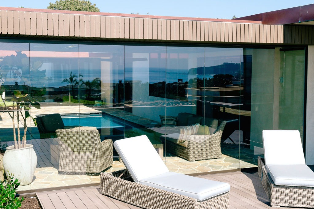 Enclosed frameless sliding glass doors with lounge chairs in front.