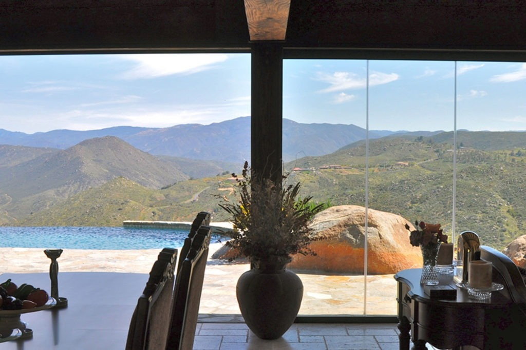 Frameless sliding glass doors with pool and view of mountains.