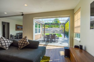 Looking from living room into backyard with enclosed frameless sliding glass doors.