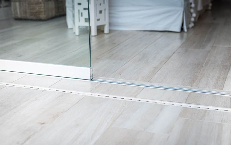 Closeup of glass door meeting wooden floor