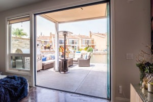 Living space with fully stacked sliding glass doors connecting to an outdoor area with table and chairs.