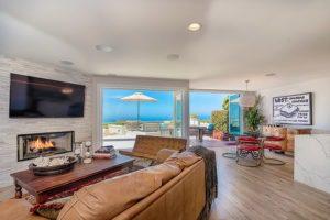 Open concept living room with folding frameless glass doors overlooking the ocean.