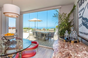 Dining room with enclosed frameless glass doors and unobstructed views of the ocean and table on patio.
