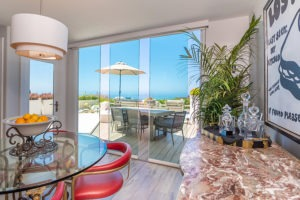Dining room with staggered frameless glass doors with unobstructed views of table on patio and ocean.