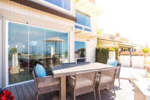 Intimate outdoor space with patio table and closed frameless glass doors.