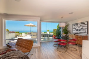 Open concept living room and dining room with wood flooring and enclosed frameless glass sliding doors with unobstructed views of the water.