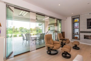 Partially open sliding glass panels connecting living space with the outdoors.