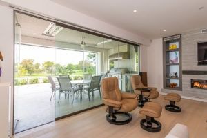 Sliding glass doors connecting a living space with the outdoors with first panel on the left open.