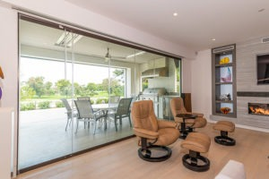 Closed frameless sliding glass doors separating a living space from patio and back yard.