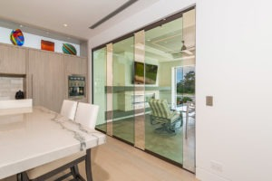 Partially open frameless sliding glass doors separating kitchen area from outdoor patio.