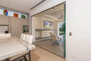 Fully open frameless sliding glass doors connecting kitchen area with patio.
