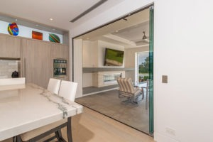 Stacked frameless glass doors on the right of the doorframe connecting kitchen area with patio.