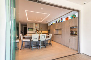 Fully stacked sliding glass doors showing a spacious kitchen and dining room.