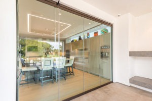 Closed frameless sliding glass doors showing kitchen area from patio.