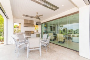 Outdoor space with round patio table and kitchenette next to closed frameless glass doors.