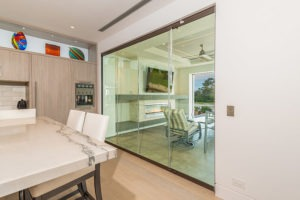 Closed frameless sliding glass doors separating kitchen area with marble table from outdoor patio.