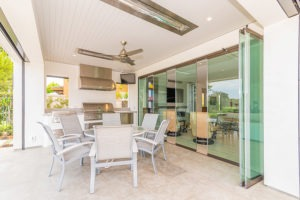 Outdoor space with round patio table and kitchenette next to partially closed frameless glass doors.