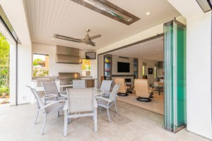 Outdoor space with round patio table and stacked frameless glass doors looking into the living room.