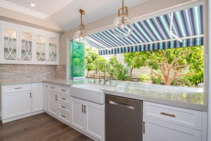 Marbled kitchen counter top with frameless glass door stacked to one side of window frame with unobstructed views of plants in backyard.