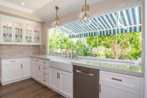 Enclosed frameless glass windows on top of marbled kitchen countertop with an unobstructed view of plants in backyard.