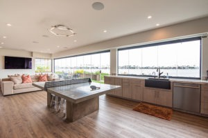 Ping pong table center of open concept kitchen and living room with enclosed frameless glass doors and windows.