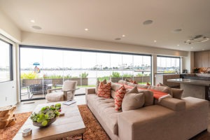 Beautifully designed open concept living room and kitchen with enclosed frameless glass doors and windows allowing for views of the boat docks.