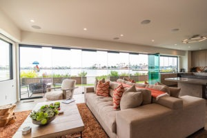 Unobstructed views of boat dock with spaced out frameless glass doors from open concept living room and kitchen.