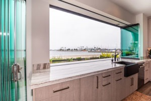 Marbled kitchen counter top with frameless glass doors and windows stacked to each side with unhindered views of the boat dock and the beach.
