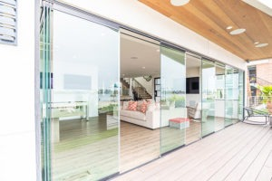 Frameless glass doors staggered in doorway between open concept living room and patio.