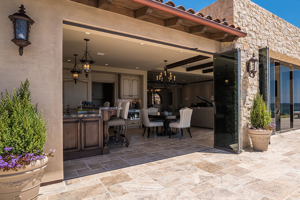 Looking into home from patio with open frameless glass doors