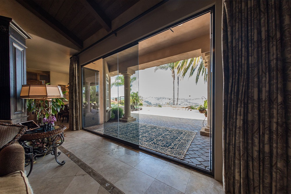Patio with three frameless glass doors slightly open